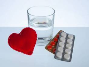 74108550-heart-glass-of-water-and-blister-packs-of-pills